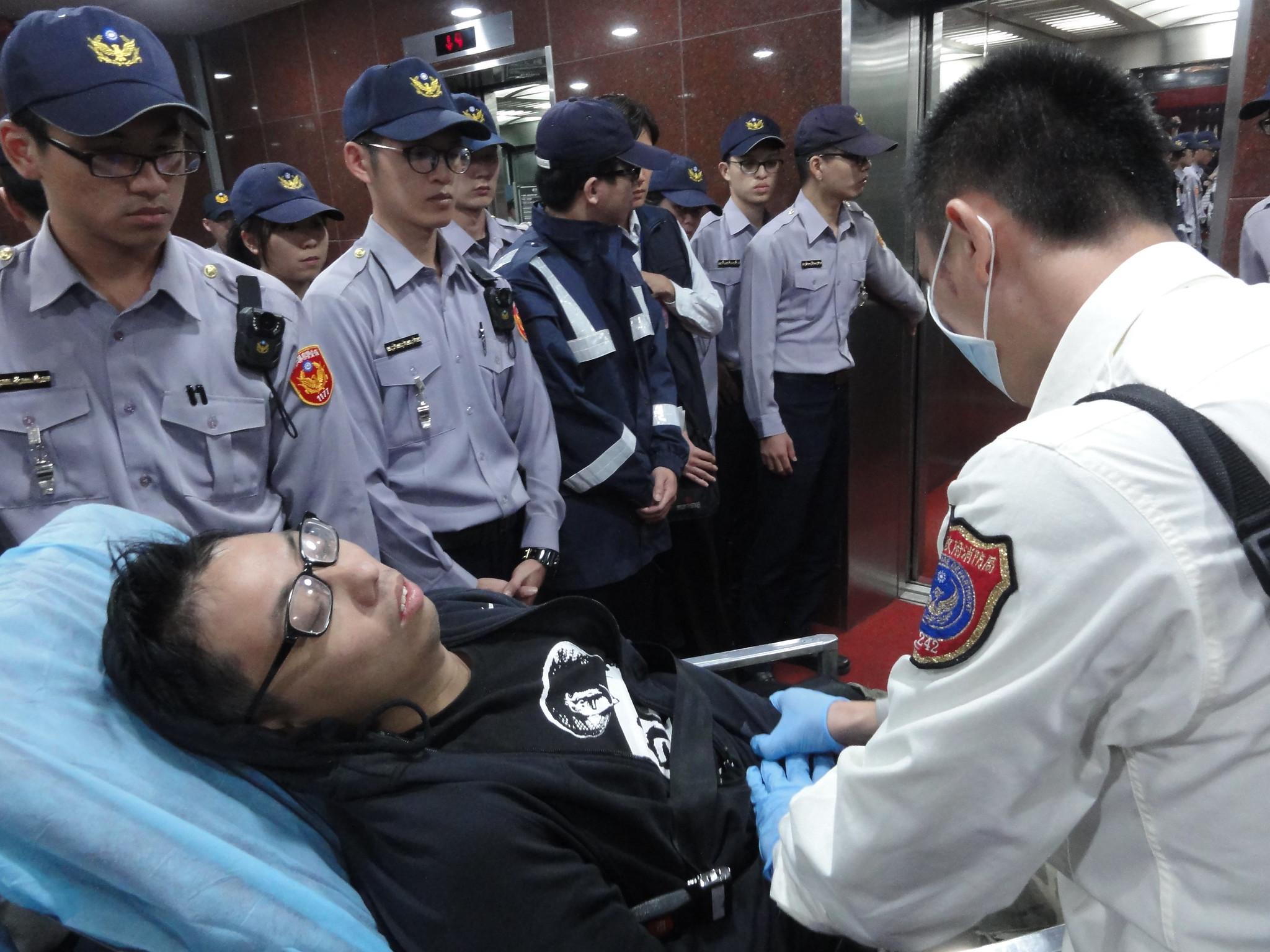 許惟棟被抬上病床緊急送醫。(攝影:張智琦)