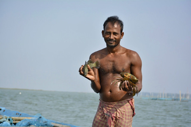 A fisherman shows a crab and a fish at Chilika.