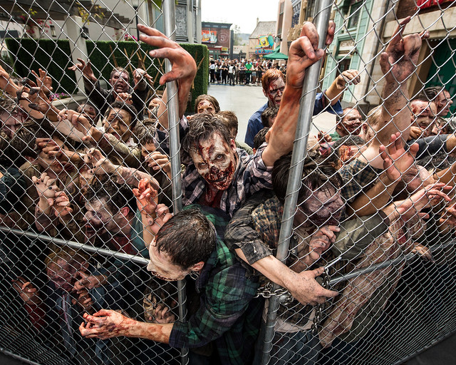 Caminantes de The Walking Dead, la serie que ha triunfado en Estados Unidos, intentando escapar en una valla