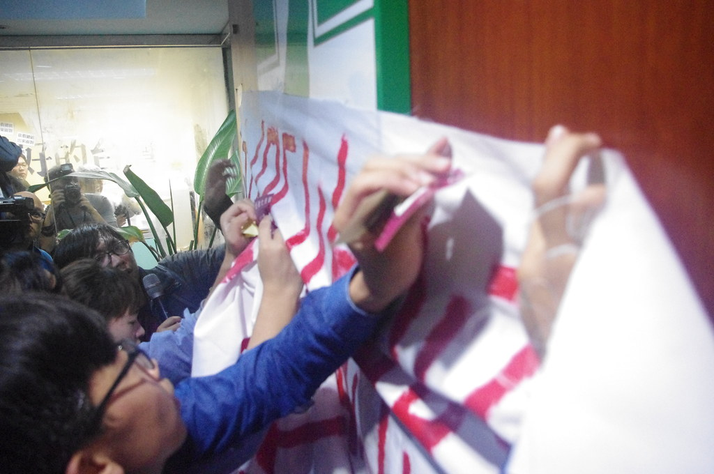 學生將「砍假總統」的布條貼在民進黨的木牌上。(攝影:高若想)
