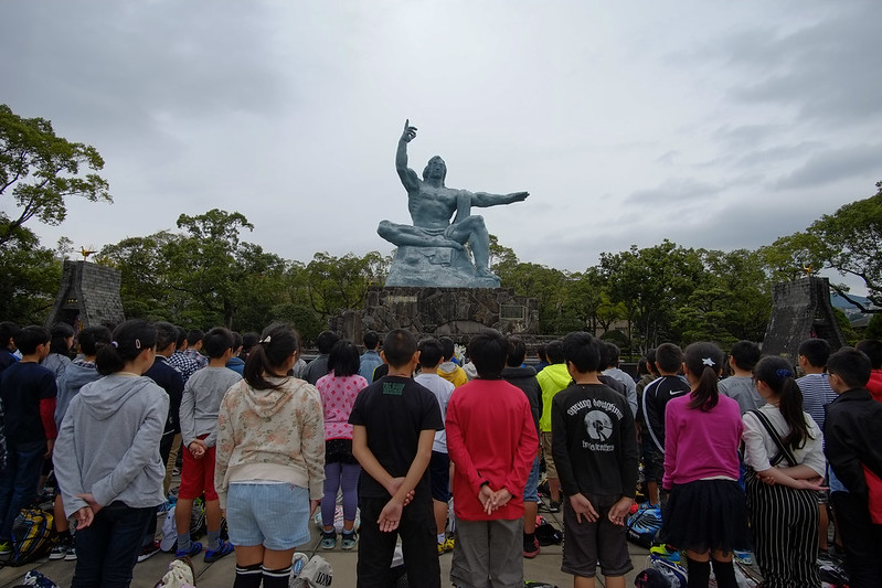 Peace Park Nagasaki. The Peace Statue has his right hand pointing to the sky to represent the threat of Nuclear weapons while the left hand symbolises eternal peace. The extended left leg and folded right leg symbolises both action when call upon and meditation and praying for the souls of those who died during the bombing.