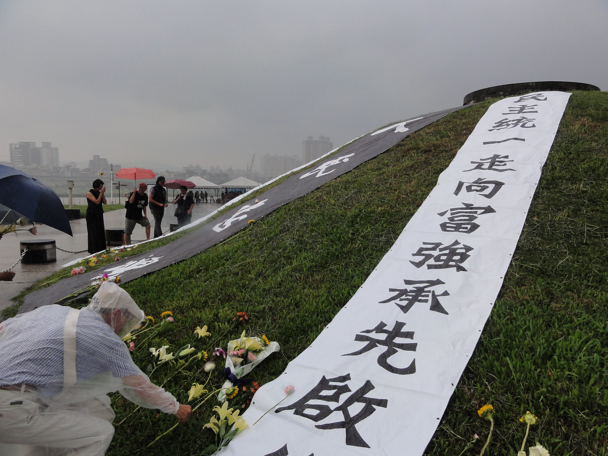秋祭尾聲天氣驟變,參與者在滂沱大雨中將鮮花圍繞放置於馬場町土丘周圍致意。(攝影:張智琦)