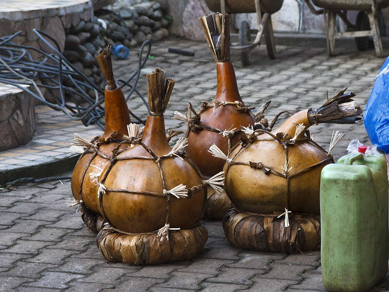 Four large calabashes corked with banana leaves contain Waragi Ugandan Homemade Gin