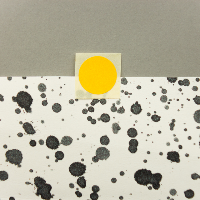 yellow sticker on splatter wallpaper