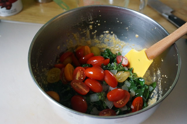 A pile of wilted greens and halved cherry tomatoes wits in the bowl of egg and cornmeal, waiting to be mixed in