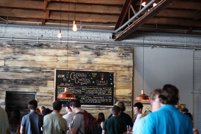 Inside the Creature Comforts brewery in Athens, Georgia. Chalkboard menu and copper lamps with a group of people standing around.