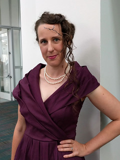 Whitney Frost Cosplay: Woman in a 1940s style purple dress, spidery cracks running down the side of her face, and hair with half a victory roll and curls on one side.