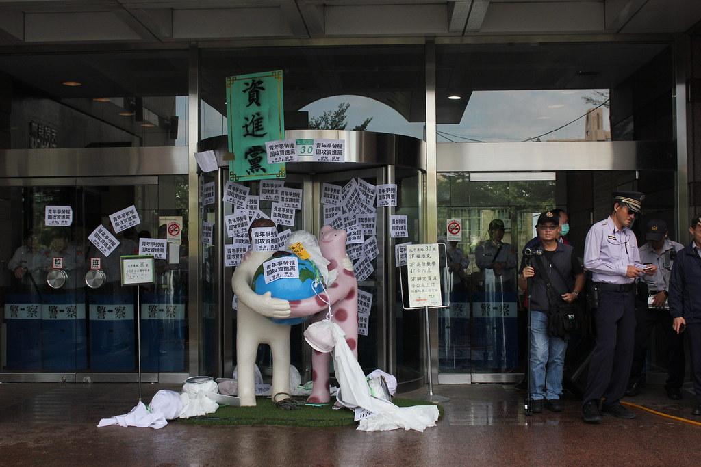 """抗议群众将写有""""青年争劳权,围攻资进党""""的标语以及""""资进党""""匾额贴在民进党部外墙。(摄影:高若想)"""