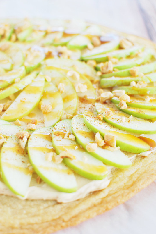 Taffy Apple Pizza - sugar cookie crust with a peanut butter and brown sugar sauce, sliced apples, chopped peanuts, and caramel sauce.