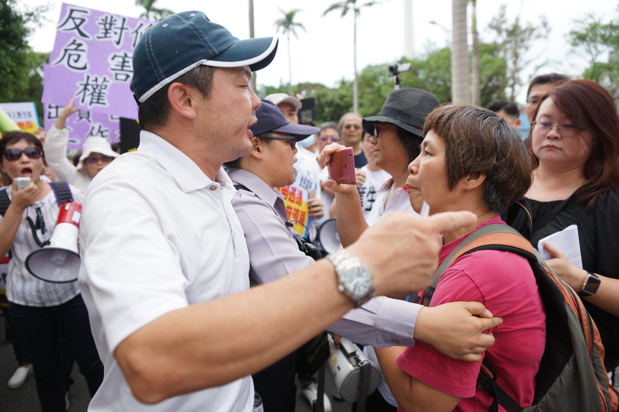 台灣國際勞工協會理事長陳素香上午持手機錄影遭仲介團體包圍。(攝影:王顥中)