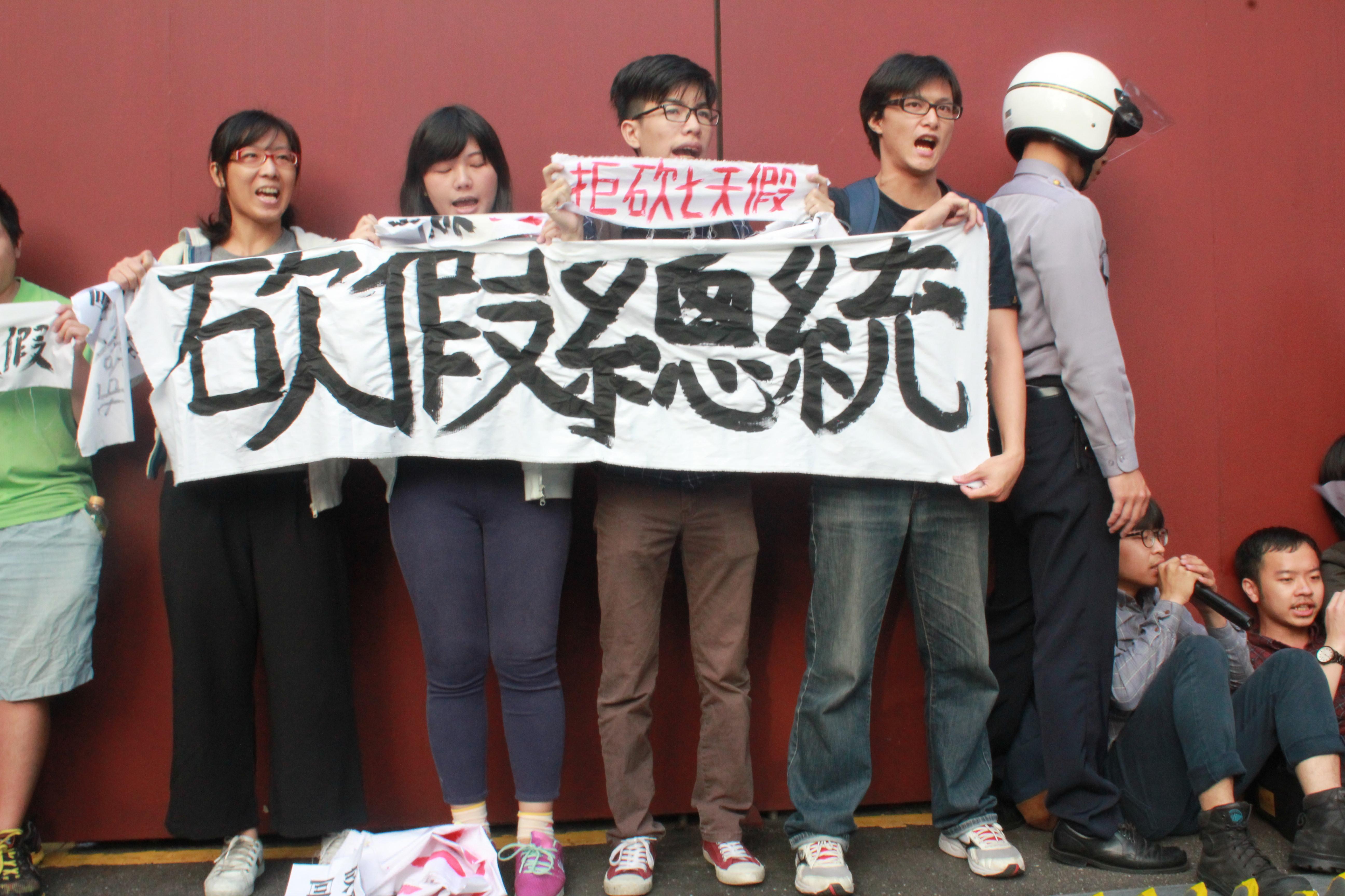 """青年团体于南海官邸拉布条""""拒砍七天假""""。(摄影:张宗坤)"""