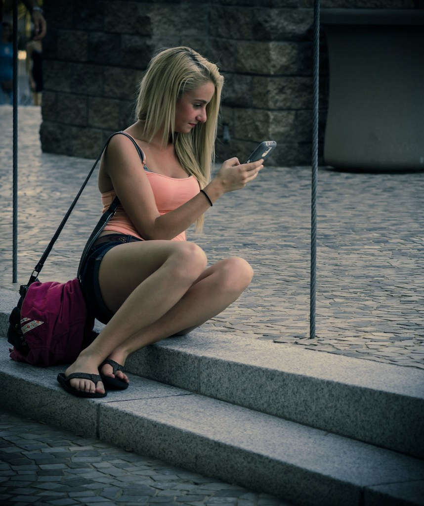 Cute girl checking out her phone on NY NY casino new front park.