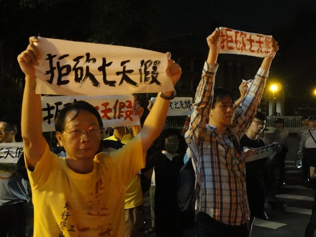 夜行軍向路過民眾高舉「拒砍七天假」標語。(攝影:張智琦)
