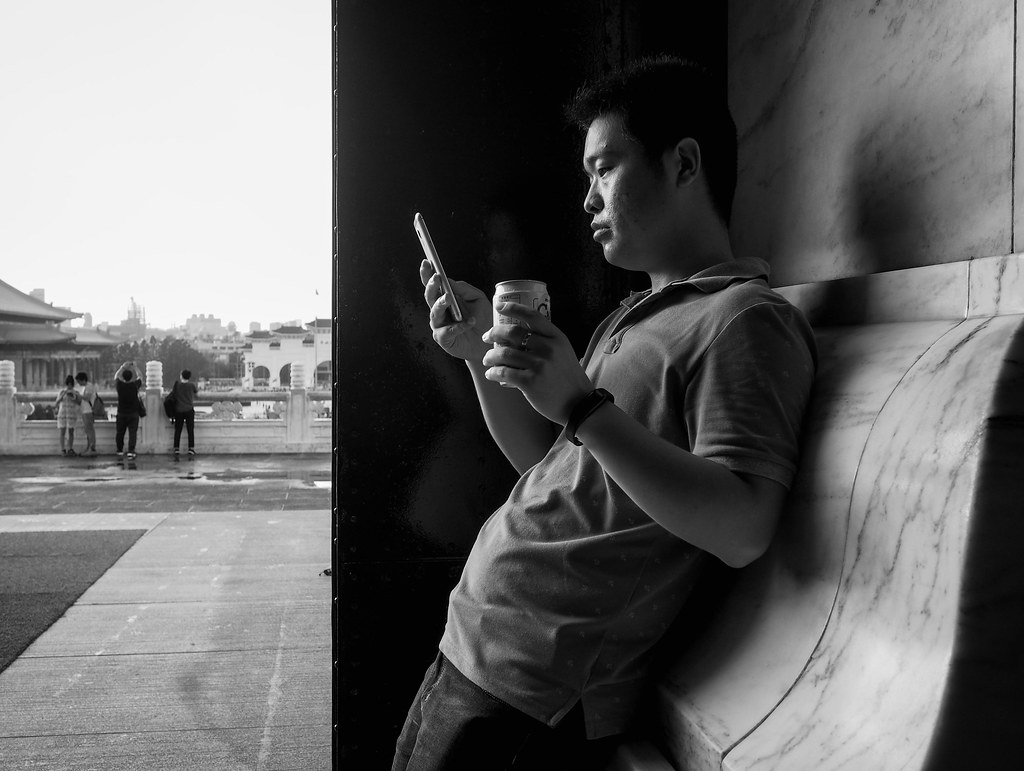 Tourist taking a phone and soda break at Chiang Kai-shek Memorial Hall in Taipei