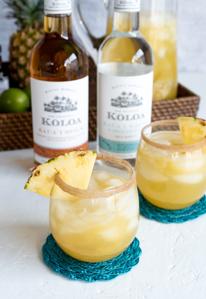 two small cocktail glasses filled with ice and rum punch cinnamon sugar rum pineapple wedges two bottles of koloa rum, brown tray with limes, whole pineapple and pitcher of rum punch
