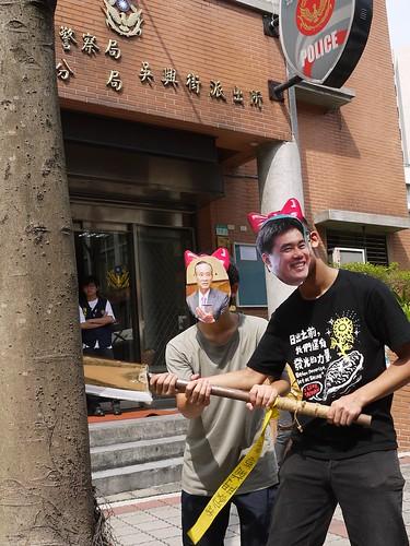 護樹志工戴上郝龍斌、趙藤雄面具,高舉金斧頭作勢要砍警局前行道樹,表示政商合作密切,成了「斧頭幫」