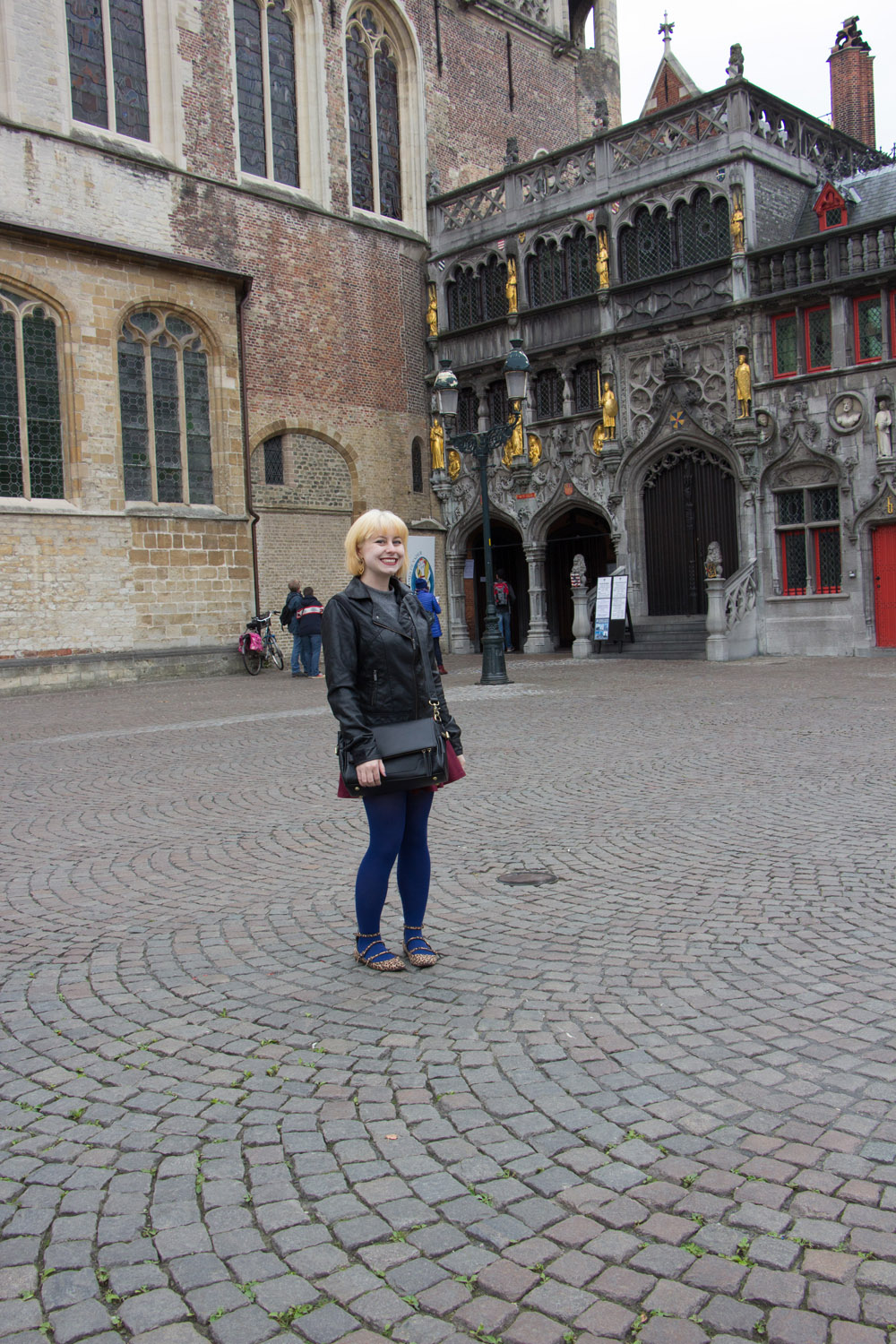 Bruges Travel Outfit wearing Leather Jacket Flippy Skirt Blue Tights and Flats