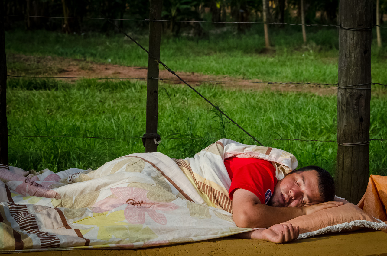 Un vendedor ambulante descansa en la vía pública luego de terminar de construir su puesto de venta de comidas. Repone energías para afrontar la larga noche de actividad y hacinamiento de clientes. (Elton Núñez).