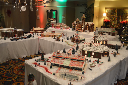 A gingerbread village is displayed on tables in the lobby of a hotel.