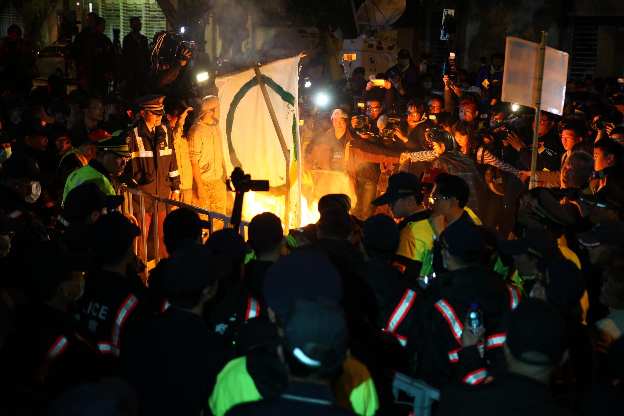 """劳团在立院外焚烧""""点亮彩立方""""旗帜与冥纸。(摄影:陈逸婷)"""