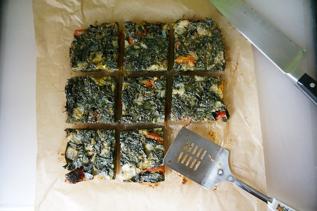 Eight squares of frittata laid out in a precise 3x3 grid on parchment paper. The lower-right square is missing; a square metal spatula rests in its space.