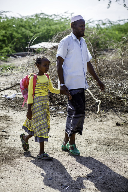 Ali Faraa, 57, walks his daughter Hussini ali Faraa, 8, to Awash city ABEC (Alternative Base Education Center)