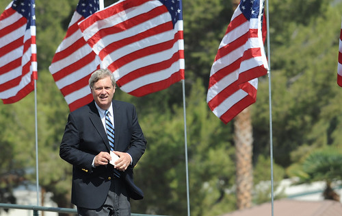 Agriculture Secretary Tom Vilsack behind a row of American flags