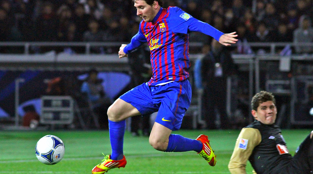 Barcelona player Lionel Messi dribbles past an opponent