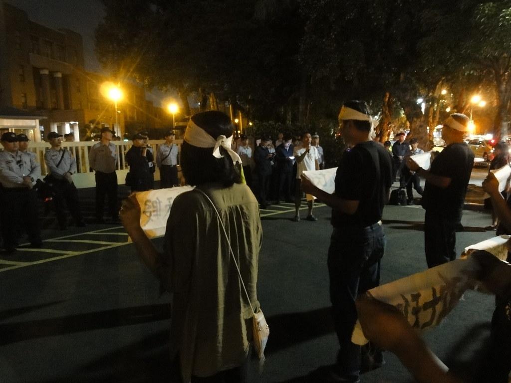 夜行軍的工人們在行政院門前和大批警力對峙。(攝影:張智琦)