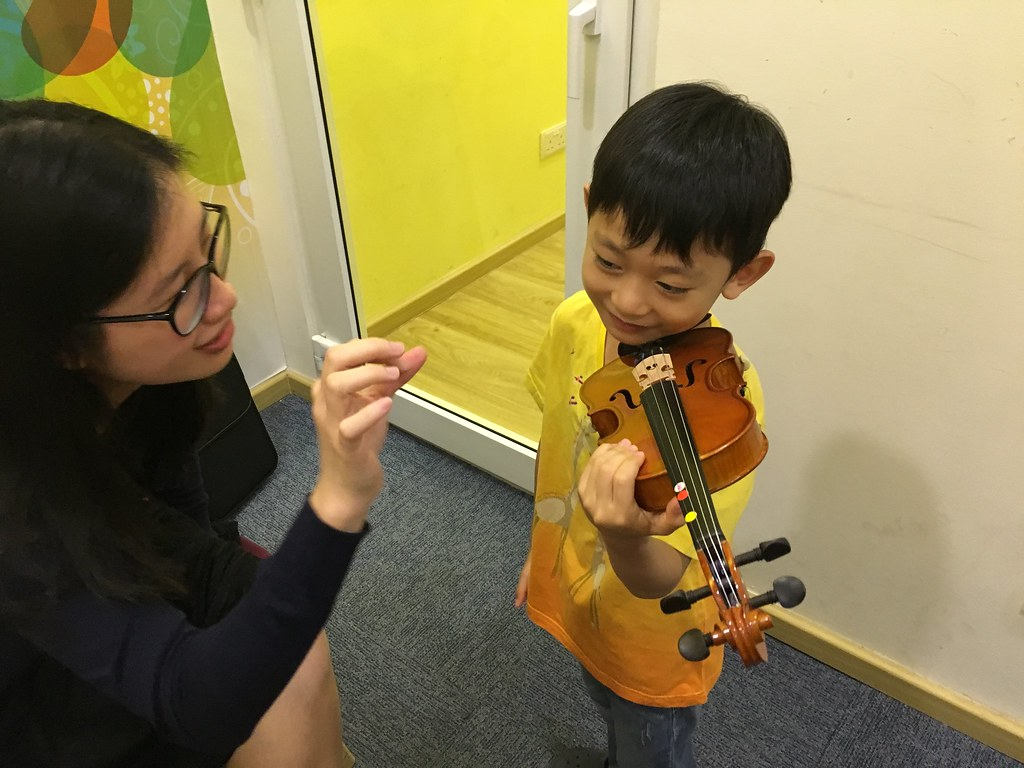 First lesson: Asher learns to hold his 1/10 violin and pluck the strings on the fingerboard.