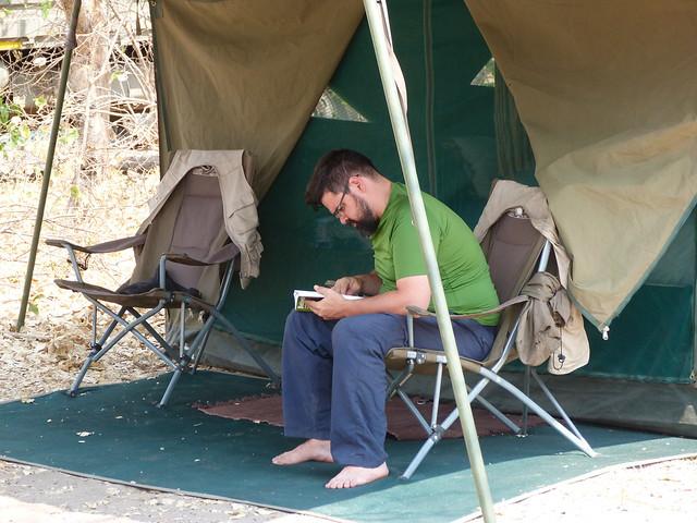 Oscar leyendo fuera de la tienda de campaña (Mopane en Botswana)