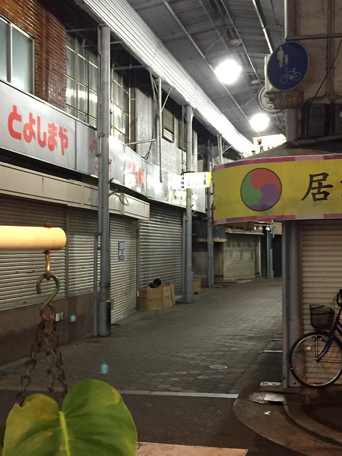 A homeless man on a street arcade in Nishinari-ku.