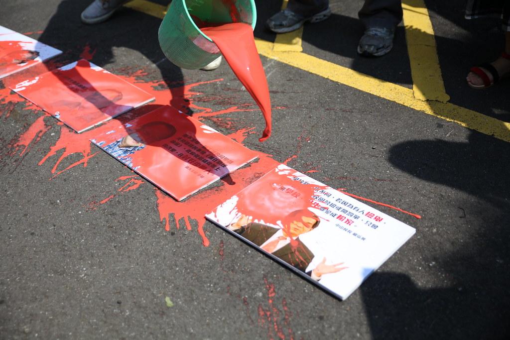 學生向印有校長相片與言論的照片潑灑象徵血汗的紅墨水,抗議校長聯合剝奪學生助理的勞動權益。(攝影:陳逸婷)