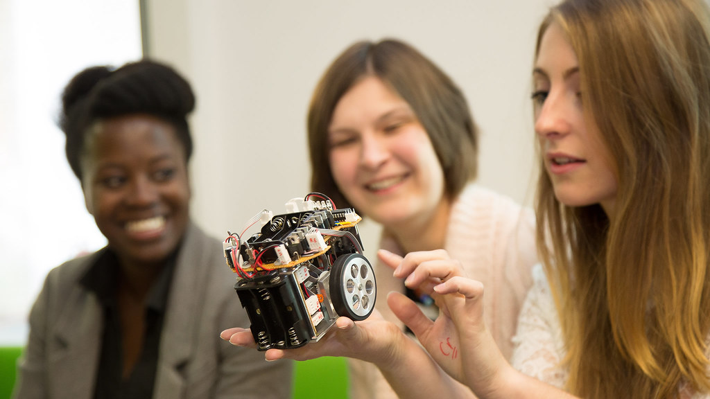 Charlotte Thomas shows engineering prototype to members of Bath's Students' Women's Engineering Society.