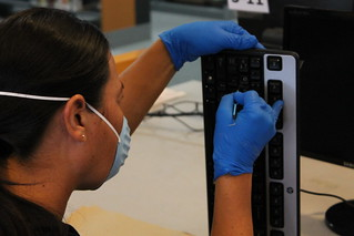 Person in a surgical mask cleaning a keyboard with a dental tool