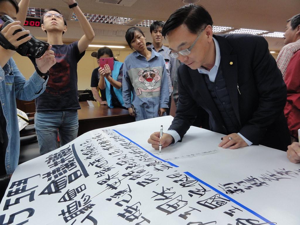 會議後,眾人簽署「拒絕刪減勞工國定假日,應修法保障國定假不少於19天」的會議共識,國民黨立委陳宜民也簽了名。(攝影:張智琦)