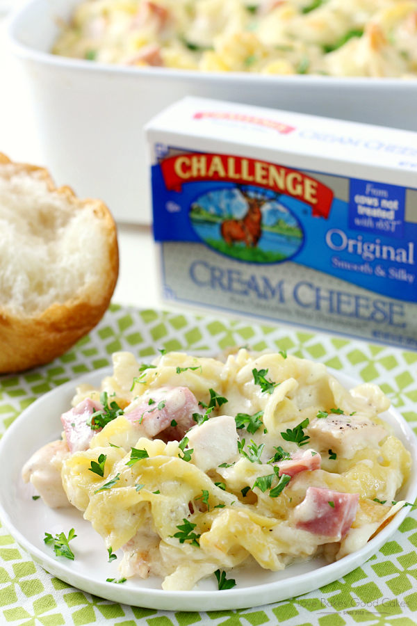 Creamy Chicken Cordon Bleu Pasta Casserole on a plate with bread and a package of Challenge Cream Cheese.