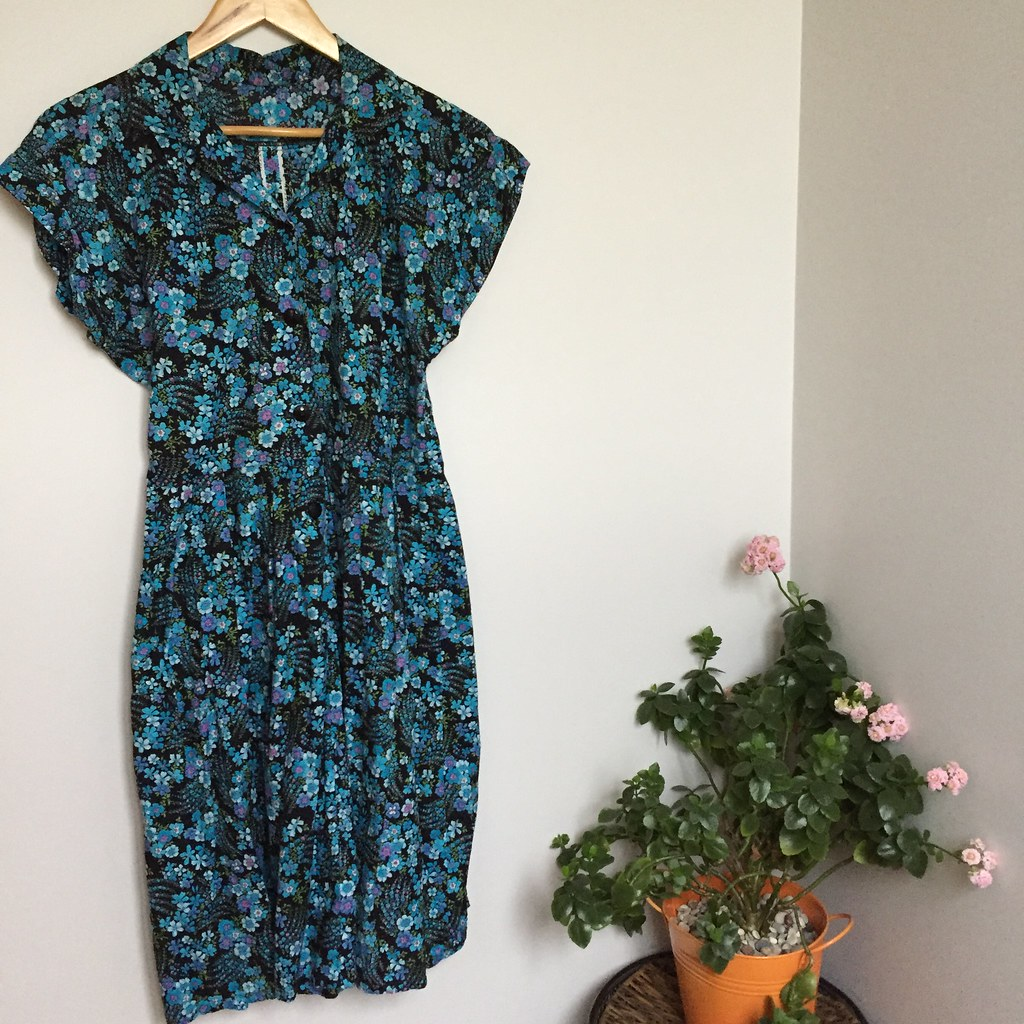 long-ish 50's style button up dress made from black based material with a blue floral print