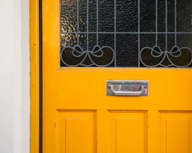 yellow door with leaded window