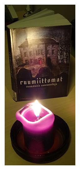 Kuva kirjasta ja kynttilästä.