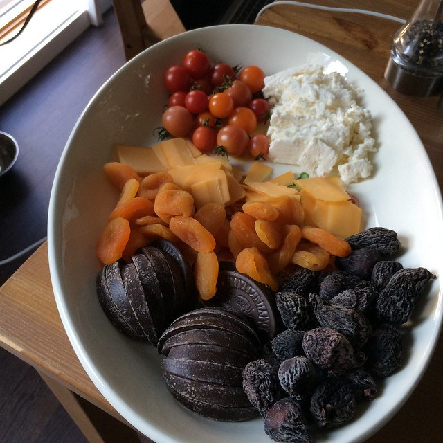 A white platter containing a broken up dark chocolate orange, dried figs, dried apricots, smoked cheddar, feta cheese, and cherry tomatoes. My contribution to an invitation to drink wine on the roof deck in 15 minutes..