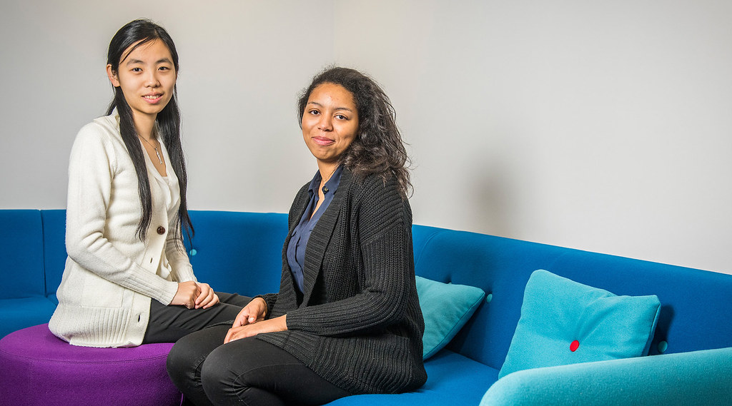 Students Naomi Clarke and Ludi Wang sitting on a sofa.