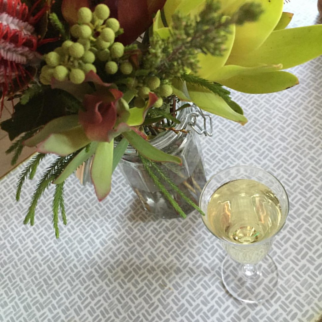 a glass of sparkling wine with a vase of natives
