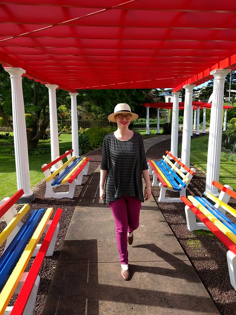 A woman stands under a pergola, wearing a draped knit tee, purple pants, and a panama hat.