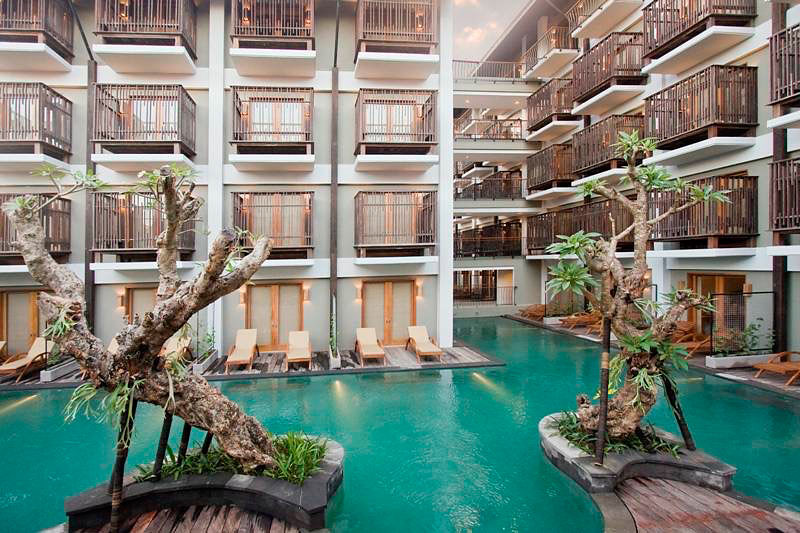 Bentuk Kolam Renang Dengan Bagian Menjorok Seperti Ceruk Dek Kayu Serta Pepohonan Yang Rimbun Menambah Kesan Alami Di Hotel Ini