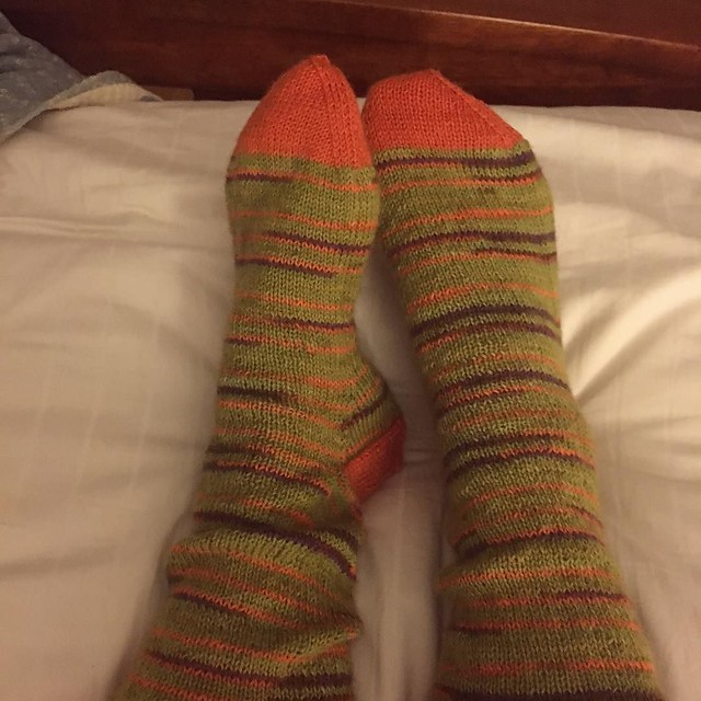 New socks, knit to/from Amsterdam. Lion Brand Sock Ease in Sourball with contrasting orange cuffs, heels and toes. #knitting #socknitting #bedsocks
