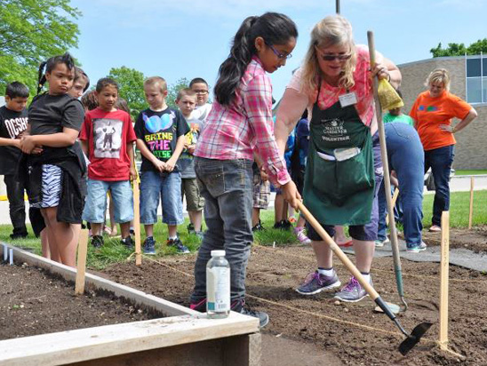 image of volunteer helping kids garden