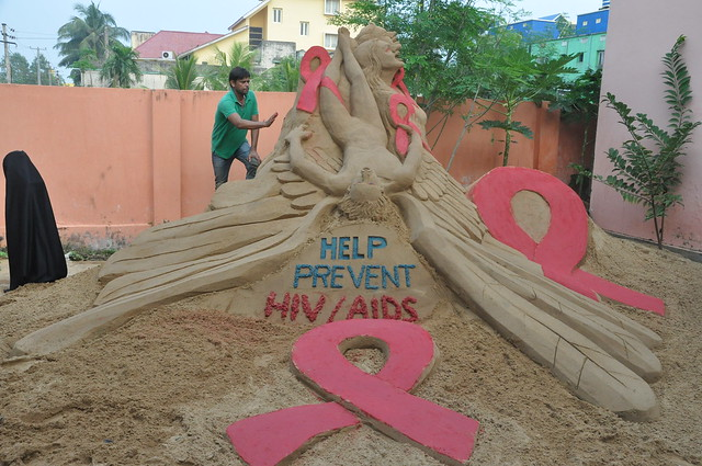 "Sand sculpture with a message ""HELP PREVENT AIDS/HIV"" on beach puri"