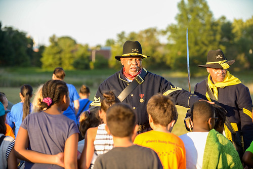 A member of the Buffalo Soldiers of the American Northwest talking to fourth graders
