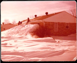 Our neighbor's house, the Kemps, had a leeward side snowdrift that went to their rooftop. That's my brother Kevin sitting on the gutters.